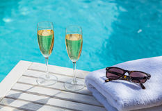 Champagne at the pool. Two glasses of champagne on a white wooden table next to the swimming pool in summer Royalty Free Stock Images