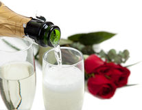 Champagne poring into glasses with roses stock images