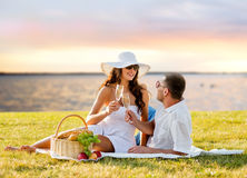 Champagne potable de couples heureux sur le pique-nique Image stock