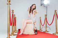 Champagne potable de femme sur le tapis rouge Photos stock