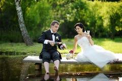 Champagne potable de jeunes mariés Photographie stock