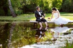 Champagne potable de jeunes mariés Photographie stock libre de droits