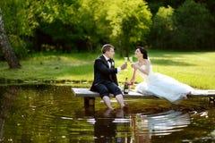 Champagne potable de jeunes mariés Images stock