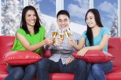 Champagne potable de personnes heureuses sur le divan Photographie stock libre de droits