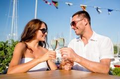 Champagne potable de sourire de couples au café Photographie stock