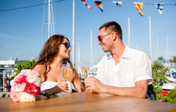 Champagne potable de sourire de couples au café Image libre de droits