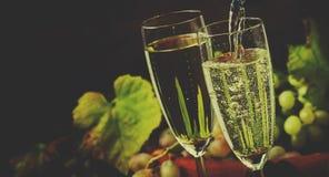 Champagne Pour In Glass druvor med vinrankan, tappningträ Backgrou arkivfoto