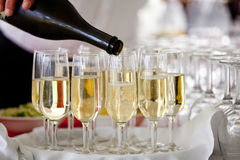 Champagne pour into glasses. A waiter pours champagne into wine glasses during a wedding celebration Stock Photo