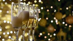 Champagne poured in flutes light background, new year christmas tree background stock video
