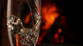 Champagne is poured into a glass on a background of fire stock video