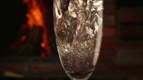 Champagne is poured into a glass on a background of fire stock footage