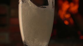 Champagne is poured into a glass on a background of fire stock video footage