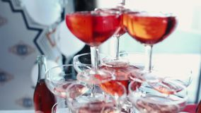 Champagne is poured into glasses. a row of glasses filled with champagne are lined up ready to be served stock video footage