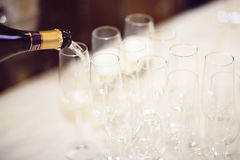 Champagne Pouring. Bottle of champagne being poured into flute glasses on a table Royalty Free Stock Images