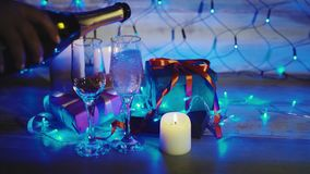 Champagne pouring from the bottle christmas decor with gifts and candles. Two flutes with sparkling wine bokeh blinking background. 4K stock footage