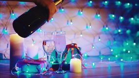 Champagne pouring from the bottle in couple of wineglasses christmas scene. Close up bokeh blinking background slow motion video full hd stock footage