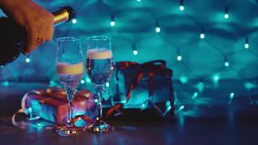 Champagne pouring from the bottle, two flutes with sparkling wine bokeh blinking. Champagne pouring from the bottle christmas decor with gifts and candles. Two stock video