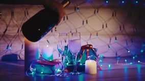 Champagne pouring from the bottle, two flutes with sparkling wine bokeh blinking. Champagne pouring from the bottle in couple of wineglasses christmas scene stock video