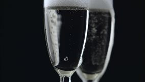 Champagne pouring from bottle into two glasses on black background. Close up. Champagne pouring from bottle into two glasses overflowing their edges on a black stock video