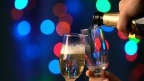 Champagne Pouring de la botella Dos flautas con el vino espumoso sobre fondo del centelleo de Bokeh del día de fiesta metrajes