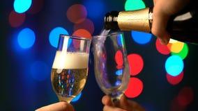 Champagne Pouring de la botella Dos flautas con el vino espumoso sobre fondo del centelleo de Bokeh del día de fiesta almacen de video