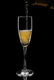 Champagne pouring in glass from bottle isolated on black backgro Royalty Free Stock Image