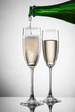 Champagne pouring into glass on white Stock Image