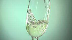 Champagne pouring into a glass on light blue background, slow motion hd video stock footage