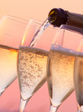 Champagne Pouring. Into glasses with a sunset background Royalty Free Stock Photos