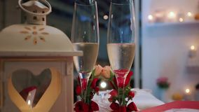 Champagne Pouring on Table. Two Flutes with Sparkling Wine over Holiday Bokeh Blinking Background. Couple of champagne Glasses closeup. Success celebrating stock footage