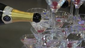 Champagne pouring in two glasses from a bottle. Two Champagne Glass On Defocused. Pouring champagne into fancy glasses stock video footage
