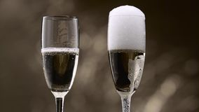 Champagne pouring in two glasses of steamy green bottle. Bokeh background. Close up. Champagne pouring in two glasses of steamy green bottle it poured over the stock video footage