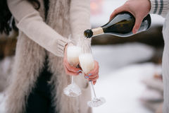 Champagne pouring in two glasses. winter forest Stock Photography