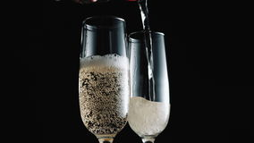 Champagne pouring into wineglasses. Champagne pouring into two transparent wineglasses isolated on black background stock video