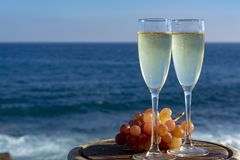 Champagne, prosecco or cava served with pink grape in two glasses on outside terrace with sea view royalty free stock photo