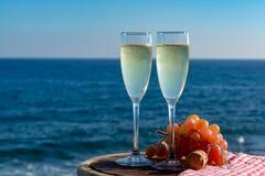 Champagne, prosecco ou cave servis avec du raisin rose en deux verres sur la terrasse extérieure avec la vue de mer images stock