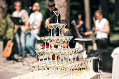 Champagne pyramid on event, party or banquet. cherry in the glass. the band in the background Stock Images