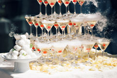 Champagne pyramid on event, party or banquet. cherry in the glass. Dry ice floats Royalty Free Stock Images