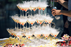 Champagne pyramid on event, party or banquet. cherry in the glass. Dry ice floats Royalty Free Stock Photos