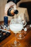Champagne que derrama em dois vidros Fotos de Stock
