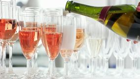 Champagne que derrama nos vidros, mão da mulher que guarda a garrafa e que derrama o champanhe cor-de-rosa nos vidros vídeos de arquivo