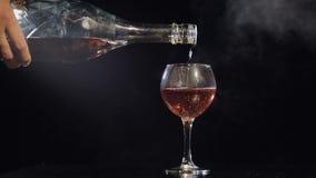 Champagne rose se renversant de bouteille dans le verre Fond noir Mouvement lent banque de vidéos