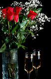 Champagne and Roses. Beautiful bouquet of red roses in a vase with two champagne glasses Royalty Free Stock Photo