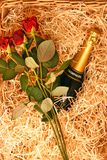 Champagne and roses. Basket with champagne and red roses Stock Photo