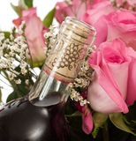 Champagne and Roses. Closeup view of a corked bottle of champagne and some pink roses stock photos