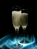 Champagne and Satin. Two tall glasses of bubbling champagne on soft blue satin. Image goes to black at top for easy text expansion Royalty Free Stock Photo