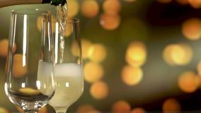 Champagne scintillante di versamento nella flauto sopra il fondo dorato di lampeggiamento di festa video d archivio