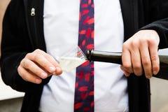 Champagne se renversant dans un verre sur une célébration de mariage Photographie stock