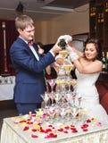 Champagne se renversant de jeunes mariés dans le verre Pyramide de champagne Images stock