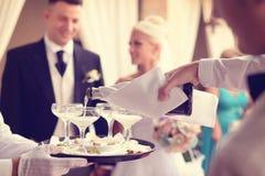 Champagne se renversant de serveur dans les verres Image stock
